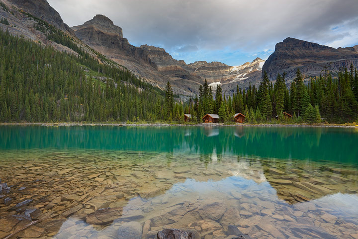 Mount Lefroy and Glacier peaks tower over the deluxe cabins reflecting in the turquoise waters of Lake O'Hara.<br />